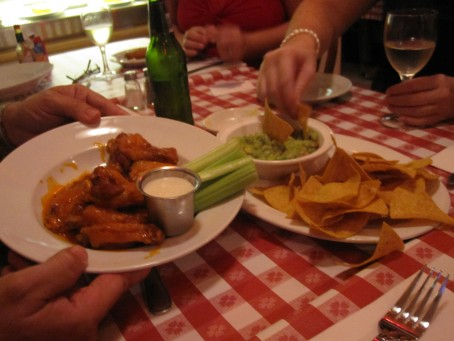 Hot wings with blue cheese dressing, and guacamole and chips