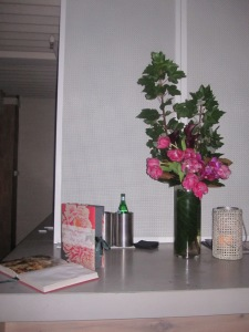 A vase filled with oriental flowers sits on the bar with a selection of Neil Perry's cook books